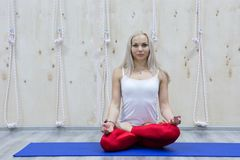 Young attractive woman practicing yoga, sitting in Padmasana exercise royalty free stock photography