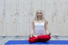 Young attractive woman practicing yoga, sitting in Padmasana exercise royalty free stock photo