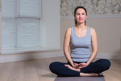 Young attractive woman practicing yoga, sitting, wearing sportswear, meditation session, home interior. Young attractive woman practicing yoga, sitting, wearing royalty free stock photo