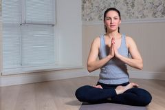 Young attractive woman practicing yoga, sitting, wearing sportswear, meditation session, home interior. Young attractive woman practicing yoga, sitting, wearing stock image