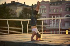 Young woman practicing yoga, standing in Pincha Mayurasana - Forearm stand in the terrace at sunset Royalty Free Stock Images