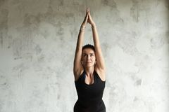 Young attractive woman in Chair pose, empty wall background. Young attractive woman practicing yoga, standing in Utkatasana exercise, Chair pose, working out Stock Images