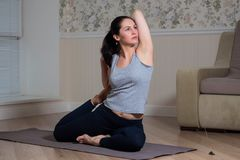 Young attractive woman practicing yoga, wearing sportswear, meditation session, home interior. Indoor meditating sitting asana balance caucasian chakra copy royalty free stock images