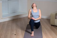 Young attractive woman practicing yoga, wearing sportswear, meditation session, home interior. Indoor meditating sitting asana balance caucasian chakra copy stock photography
