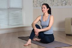 Young attractive woman practicing yoga, wearing sportswear, meditation session, home interior. Indoor meditating sitting asana balance caucasian chakra copy stock photo
