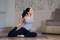 Young attractive woman practicing yoga, wearing sportswear, meditation session, home interior. Indoor meditating sitting asana balance caucasian chakra copy royalty free stock photography