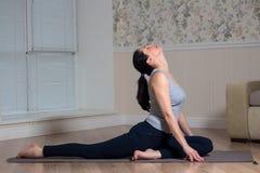 Young attractive woman practicing yoga, wearing sportswear, meditation session, home interior. Indoor meditating sitting asana balance caucasian chakra copy royalty free stock photo