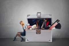 Young attractive woman pushing big hevy case with cosmetics with some difficulty royalty free stock image