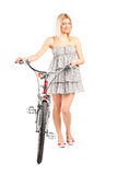 Young attractive woman pushing a bike. Full length portrait of a young attractive woman pushing a bike isolated on white background stock images