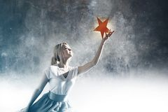 Young attractive woman reaching for the star. Take a star from the sky, dreams and plans, concept. Textured gray background royalty free stock photography