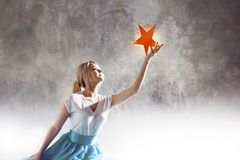 Young attractive woman reaching for the star. Take a star from the sky, dreams and plans, concept. Textured gray background royalty free stock image