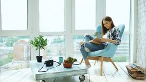 Young attractive woman read book and drink coffee sitting on balcony in modern loft apartment. Young attractive woman read book sitting on balcony in modern loft stock images