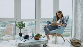 Young attractive woman read book and drink coffee sitting on balcony in modern loft apartment stock footage