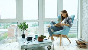 Young attractive woman read book and drink coffee sitting on balcony in modern loft apartment Stock Photography