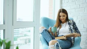 Young attractive woman read book and drink coffee sitting on balcony in modern loft apartment. Young attractive woman read book sitting on balcony in modern loft stock photography