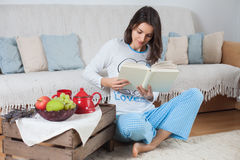 Young attractive woman, reading a book at home, eating fruits Royalty Free Stock Images