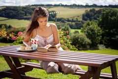 Young attractive woman, reading a book outdoor, enjoying coffee Stock Photo