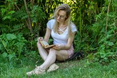 Young attractive woman reading book under the tree in park at sunny day royalty free stock photo