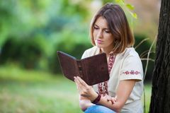 Young attractive woman reading e-book in park Stock Photo
