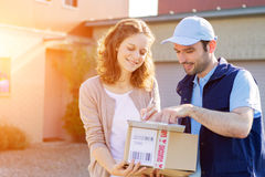 Young attractive woman receiving parcel at home Royalty Free Stock Photography