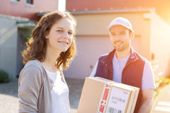 Young attractive woman receiving parcel at home Royalty Free Stock Photos