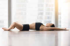 Young attractive woman in Reclined Butterfly pose against floor Stock Photo