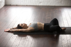 Young attractive woman in Reclined Butterfly pose, white loft st Stock Photos