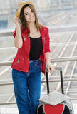 Young attractive woman in a red coat and hat standing in the terminal or at the station with a suitcase. Stock Photo