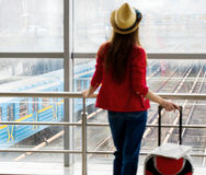 Young attractive woman in a red coat and hat standing in the terminal or at the station with a suitcase. Stock Images