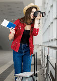 Young attractive woman in a red coat and hat standing in the terminal or at the station with a suitcase and photographs Royalty Free Stock Image