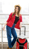 Young attractive woman in a red coat and hat standing in the terminal or at the station with a suitcase. Royalty Free Stock Image