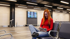 Young attractive woman with red hair and glasses use gadget in airport departure lounge Stock Image