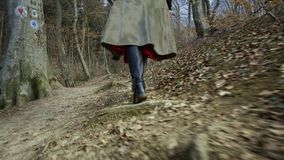 Young attractive woman with red hat wanders in forest. Young attractive woman with red hat and red skirt wanders along pathway leading trough thick forest stock footage