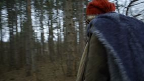 Young attractive woman with red hat wanders in forest touching tree. Young attractive woman with red hat and red skirt wanders along pathway leading trough stock video footage