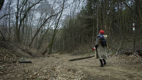 Young attractive woman with red hat wanders in forest. Young attractive woman with red hat and red skirt wanders along pathway leading trough thick forest stock video