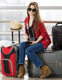 Young attractive woman in a red jacket and sunglasses sitting on suitcases in the terminal or train station. Stock Photography
