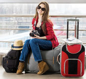 Young attractive woman in a red jacket and sunglasses sitting on suitcases in the terminal or train station. Royalty Free Stock Images