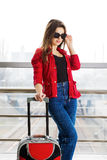 Young attractive woman in red standing in the terminal with the glasses with a suitcase. The girl met on a trip Royalty Free Stock Photo