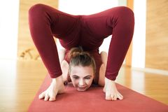 Young attractive woman in a red suit practicing yoga, standing in Scorpion exercise, vrischikasana pose, working out, wearing spor. Tswear, indoor full length in Royalty Free Stock Photography