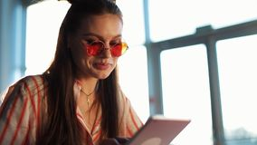 Young attractive woman in red sunglasses with tablet computer sitting in cafe. Beautiful girl in airport or shoppping stock video