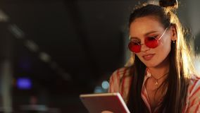 Young attractive woman in red sunglasses with tablet computer sitting in cafe. Beautiful girl in airport or shoppping stock video footage