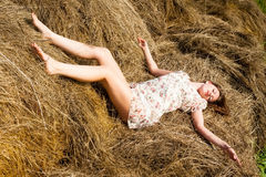 Young attractive woman relaxes on hay Stock Image