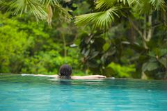 Young attractive woman relaxing happy at tropical beach luxury resort swimming at jungle infinity pool enjoying Summer holidays in stock images