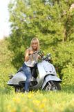 Young attractive woman riding scooter. On natural background Royalty Free Stock Image