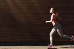 Young woman jogging in city copy space stock photo