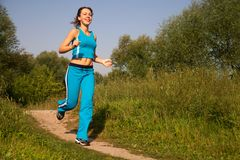 Young attractive woman runs in the country Royalty Free Stock Photography