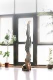 Young attractive woman in salamba sirsasana pose, home interior Royalty Free Stock Photography