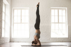 Young attractive woman in salamba sirsasana pose, white loft stu. Young attractive yogi woman practicing yoga concept, standing in salamba sirsasana exercise Stock Photo