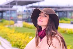 Young attractive woman in sandy coat and brown hat on, a breath of fresh air in a city Park on the waterfront.  stock photo