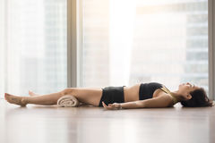 Young attractive woman in Savasana pose against floor window Royalty Free Stock Photography